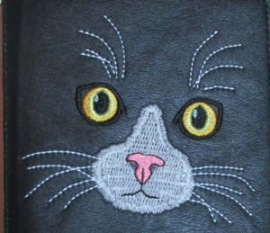 Close up of embroidered cat face on a leather journal cover. ©Suzan Houston Bessie Hyde Leather Works